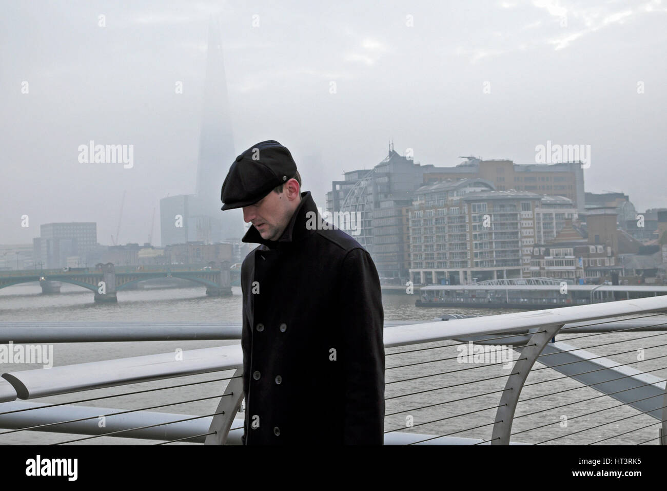 A man walking across the Millennium Bridge with a view of the Shard on a day of high air pollution winter  2017 - Stock Image