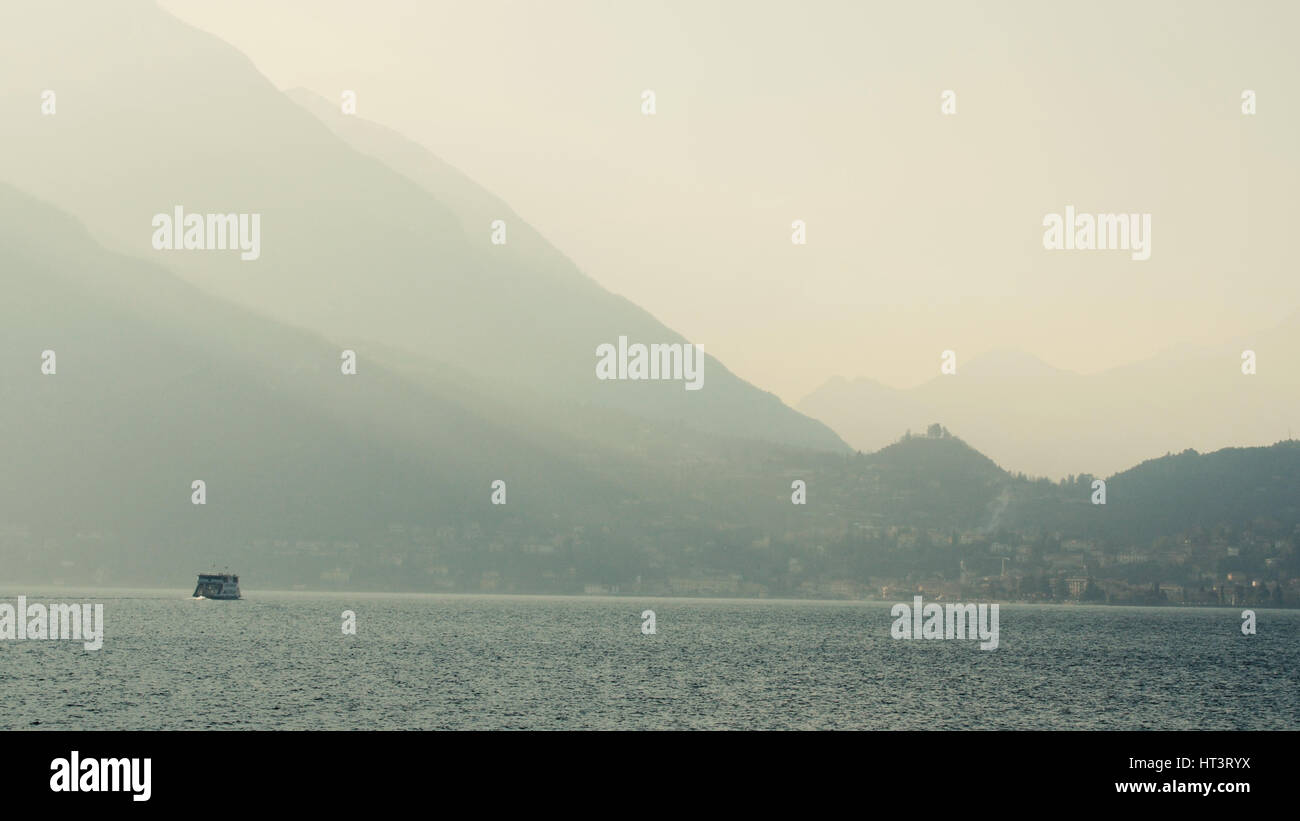 Ferry swim in the lake, contrasting the evening lighting. Lake Como, Italy. - Stock Image