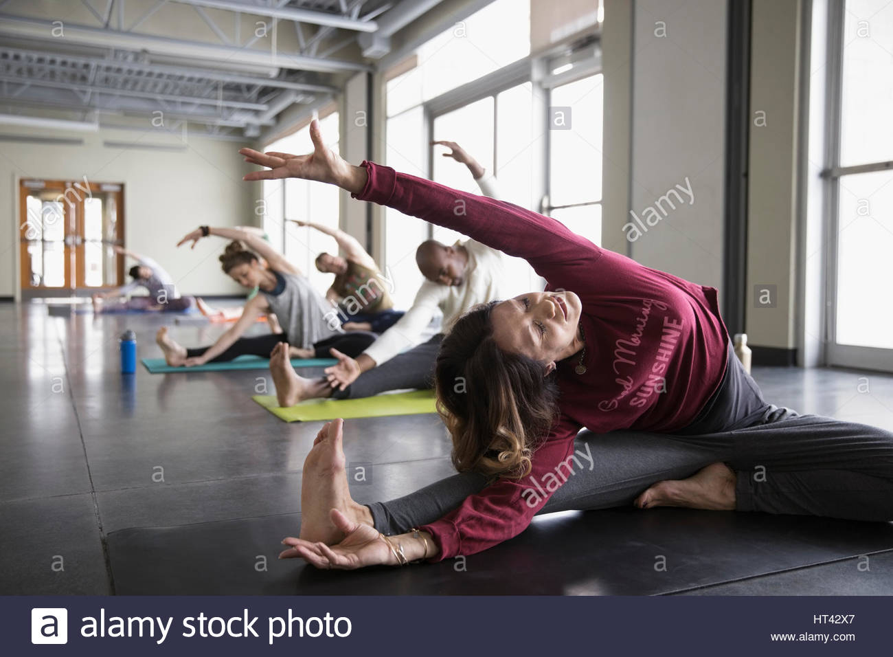 Woman practicing wide legged seated side bend in yoga class studio - Stock Image