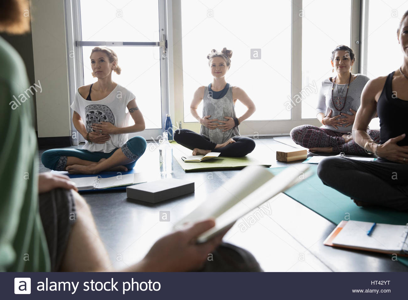 Yoga class with journals practicing breathing with hands on stomachs in yoga class studio - Stock Image