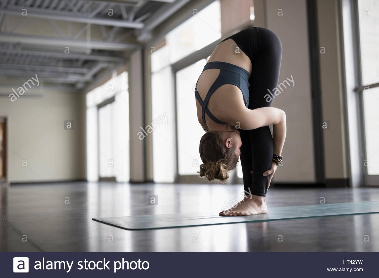 Woman practicing yoga forward fold in gym studio - Stock Image