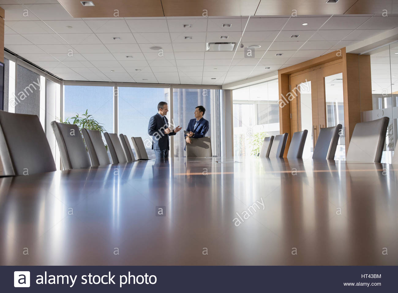 Businessmen Talking At Long Conference Table In Conference Room - Long meeting table