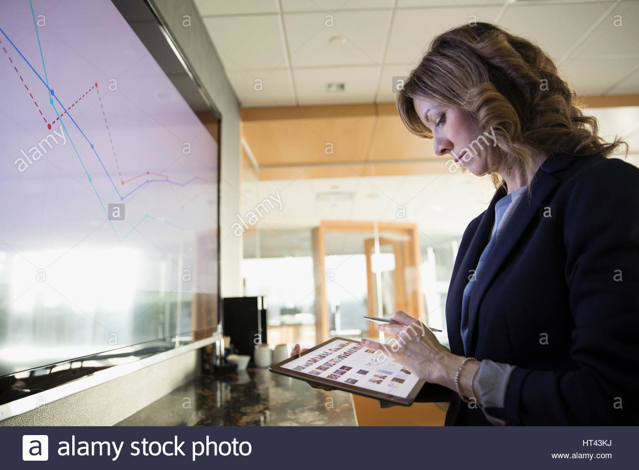 Businesswoman with digital tablet preparing audio visual presentation in conference room - Stock Image