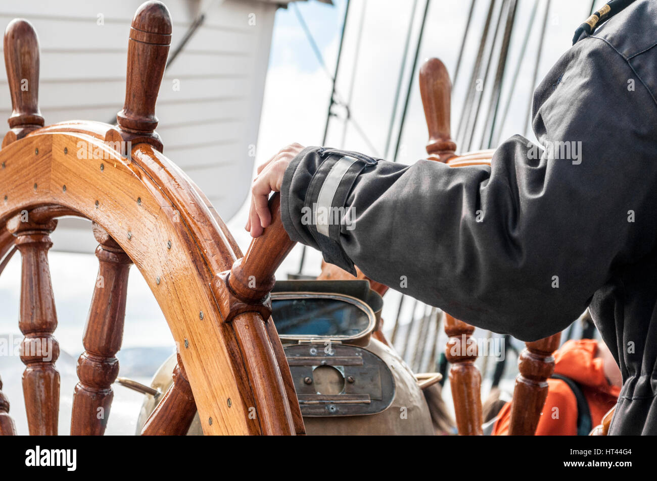 Captain behind a classic ships steering wheel - Stock Image