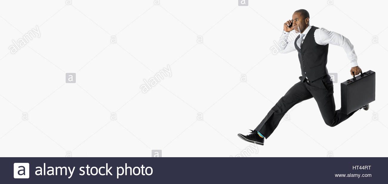 Energetic businessman running and jumping, talking on cell phone against white background - Stock Image
