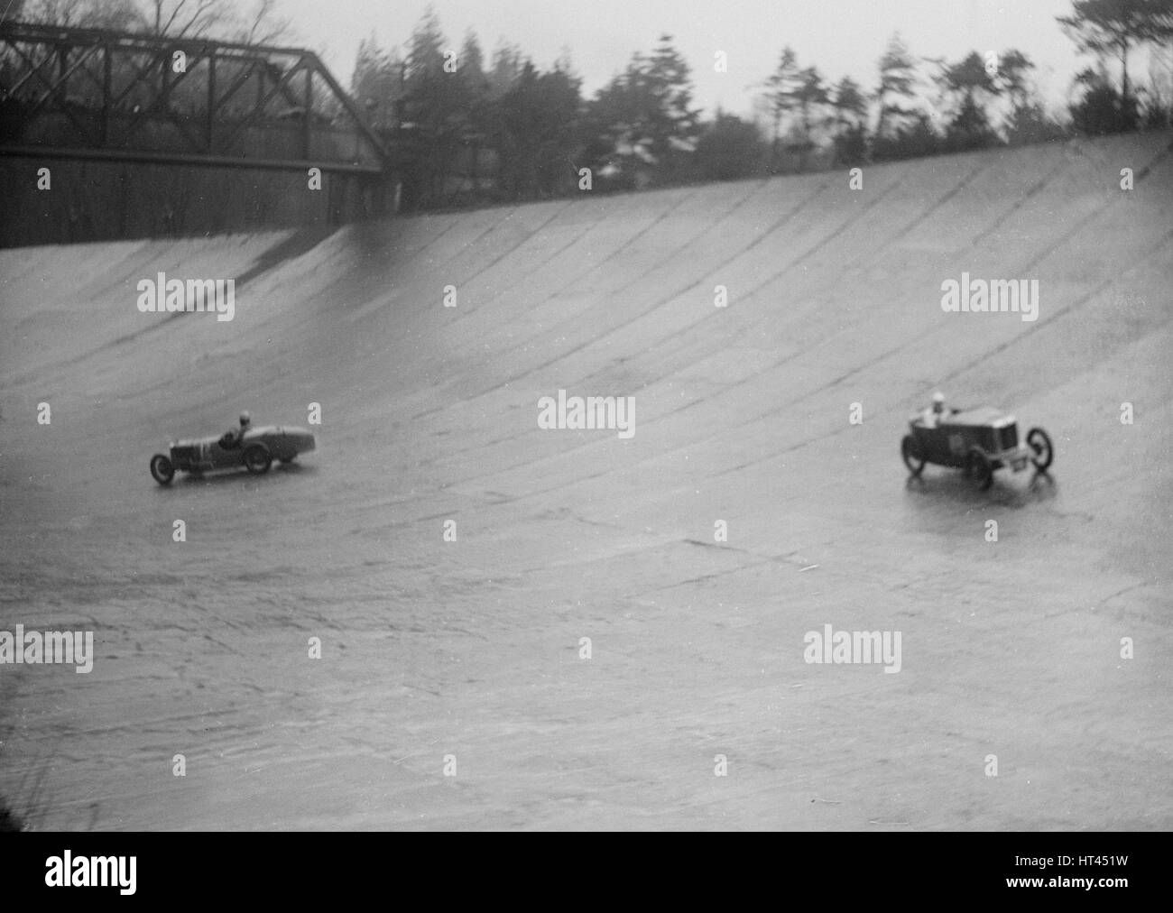 MG M type and Riley 9 Brooklands racing at a BARC meeting, Brooklands, Surrey, 1931 Artist: Bill Brunell. - Stock Image