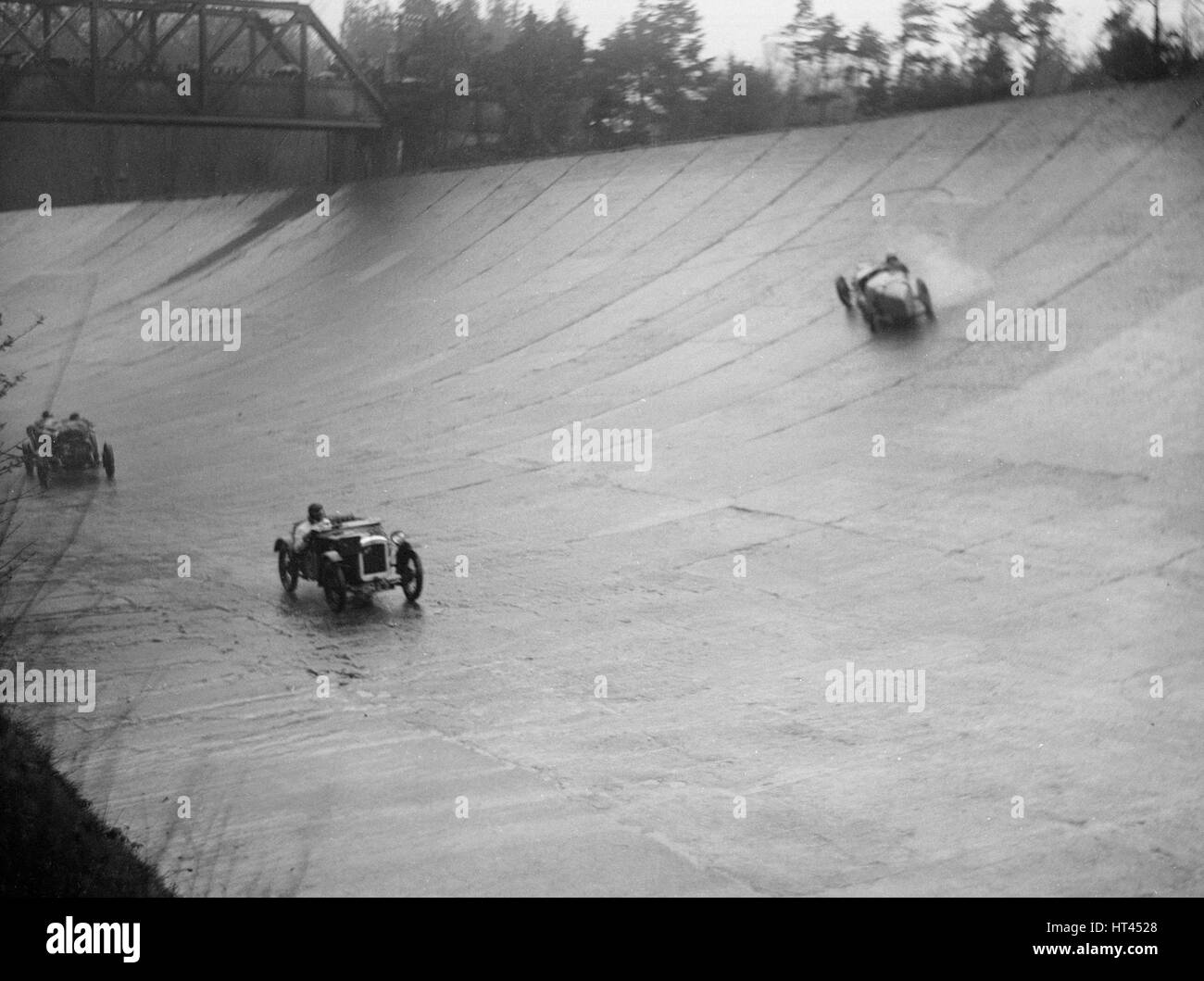 Austin 7 and the spinning Riley of HL Roberts, BARC Mountain Race, Brooklands, Surrey, 1931 Artist: Bill Brunell. - Stock Image