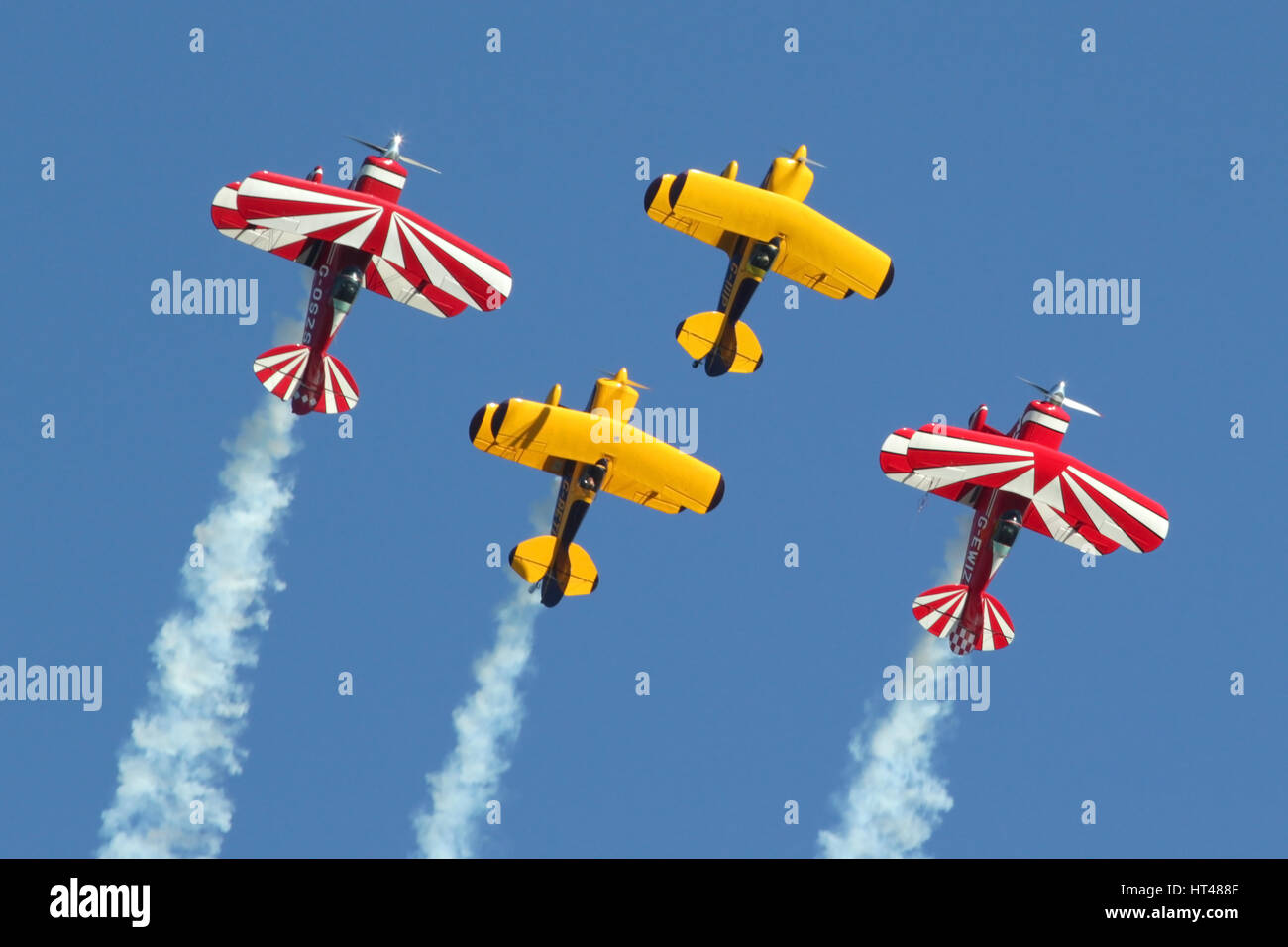 Four Pitts Special aerobatic aircraft pulling up into a loop during a Duxford airshow. - Stock Image