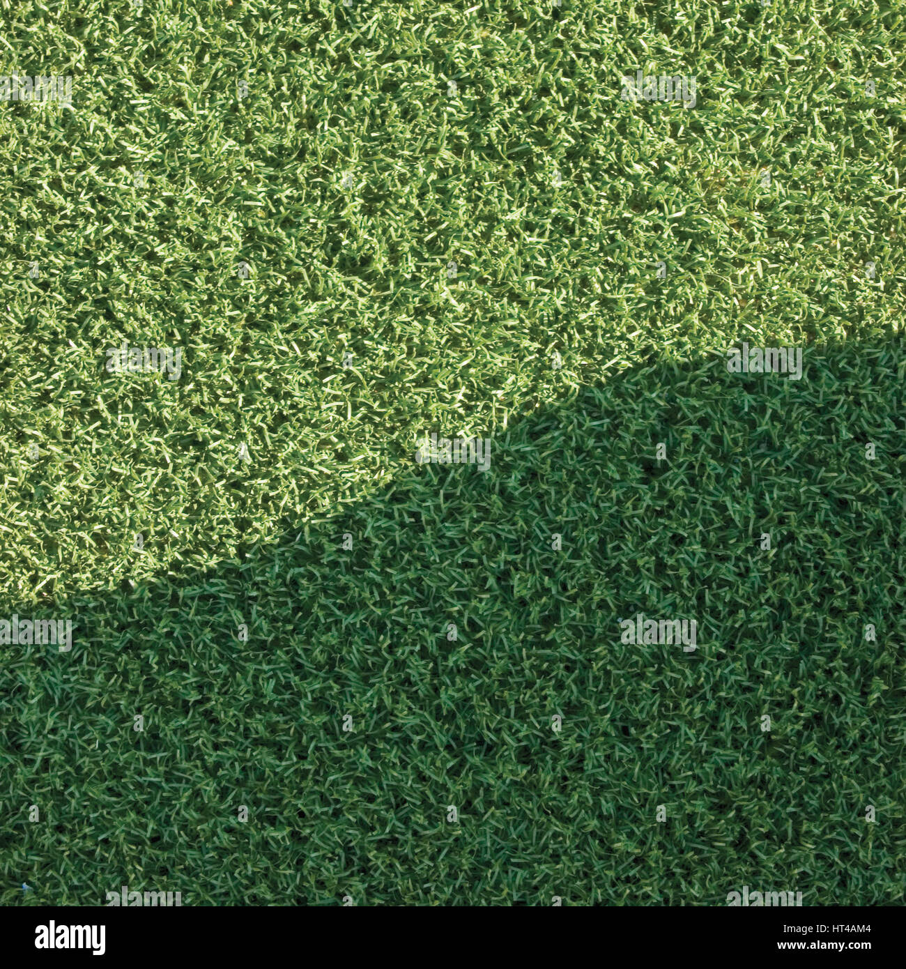 Artificial grass fake turf synthetic lawn field macro closeup with gentle shaded shadow area, green sports texture Stock Photo