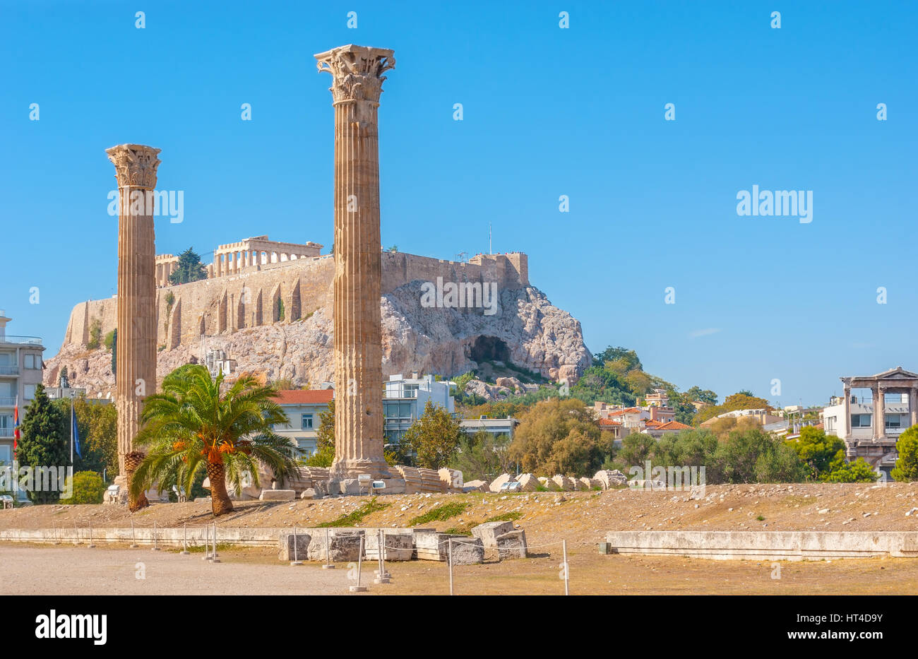 The Acropolis Hill with Parthenon on the top behind the carved stone columns of Olympian Zeus Temple, Athens, Greece - Stock Image