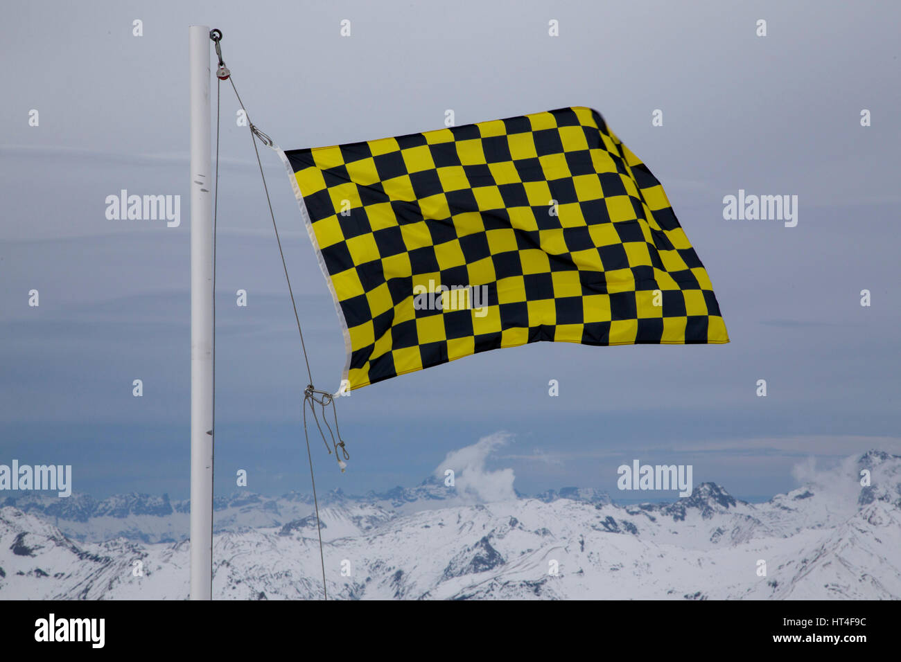 An avalanche warning flag can be seen at the French ski resort of Les Arcs. The yellow and black chequered flag - Stock Image