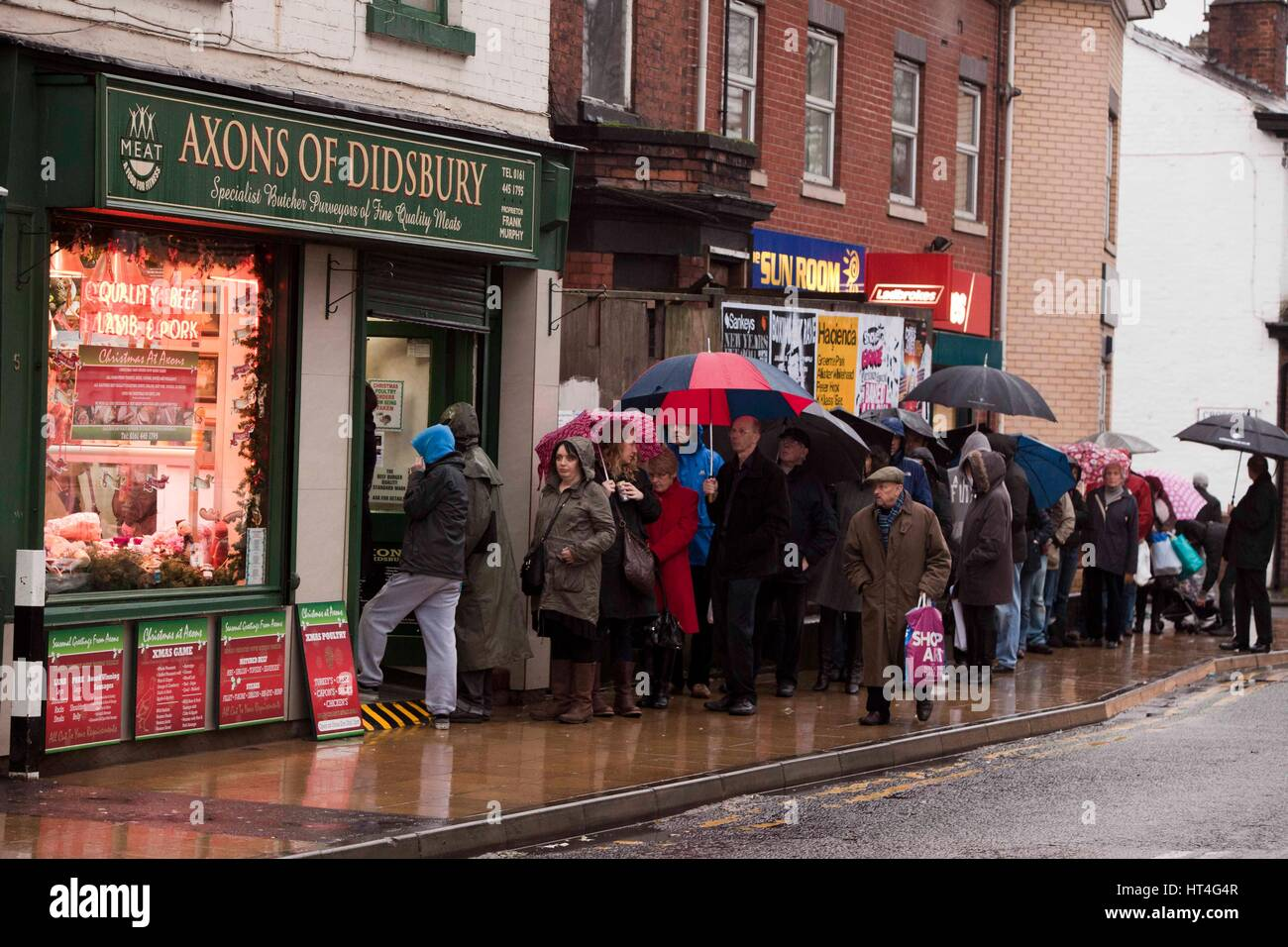 Queues of people outside a butchers shop ahead of Christmas .  Axons of Didsbury butchers - Stock Image