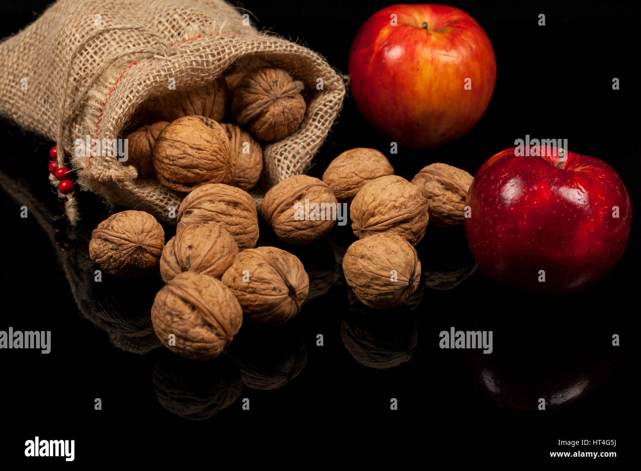 d5f59875b1ba Whole nuts with fresh red apples on a table on a black background ...