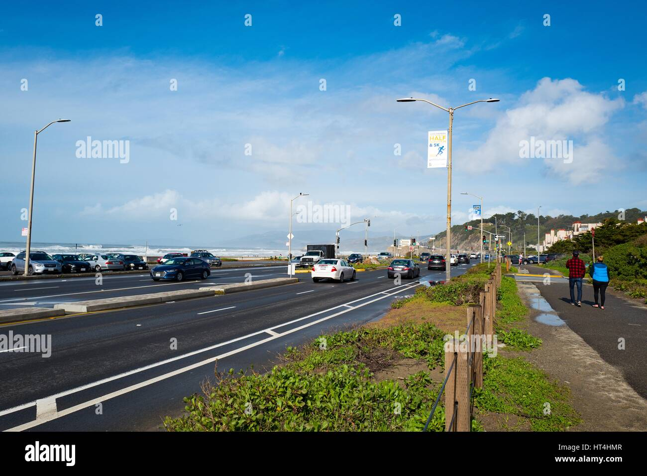 Two people stroll near the Great Highway at Ocean Beach towards the Cliff House restaurant (visible in distance) Stock Photo