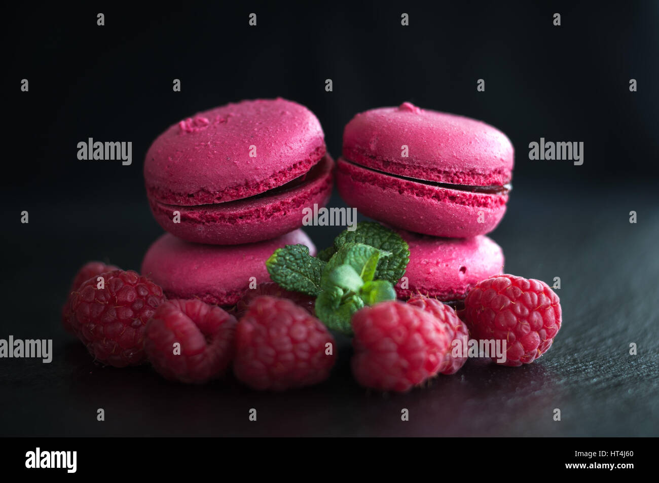 pink macaroons with raspberries on black background - Stock Image