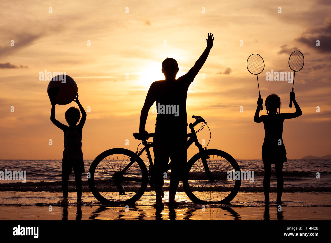 Father and children playing on the beach at the day time. Concept of friendly family. - Stock Image