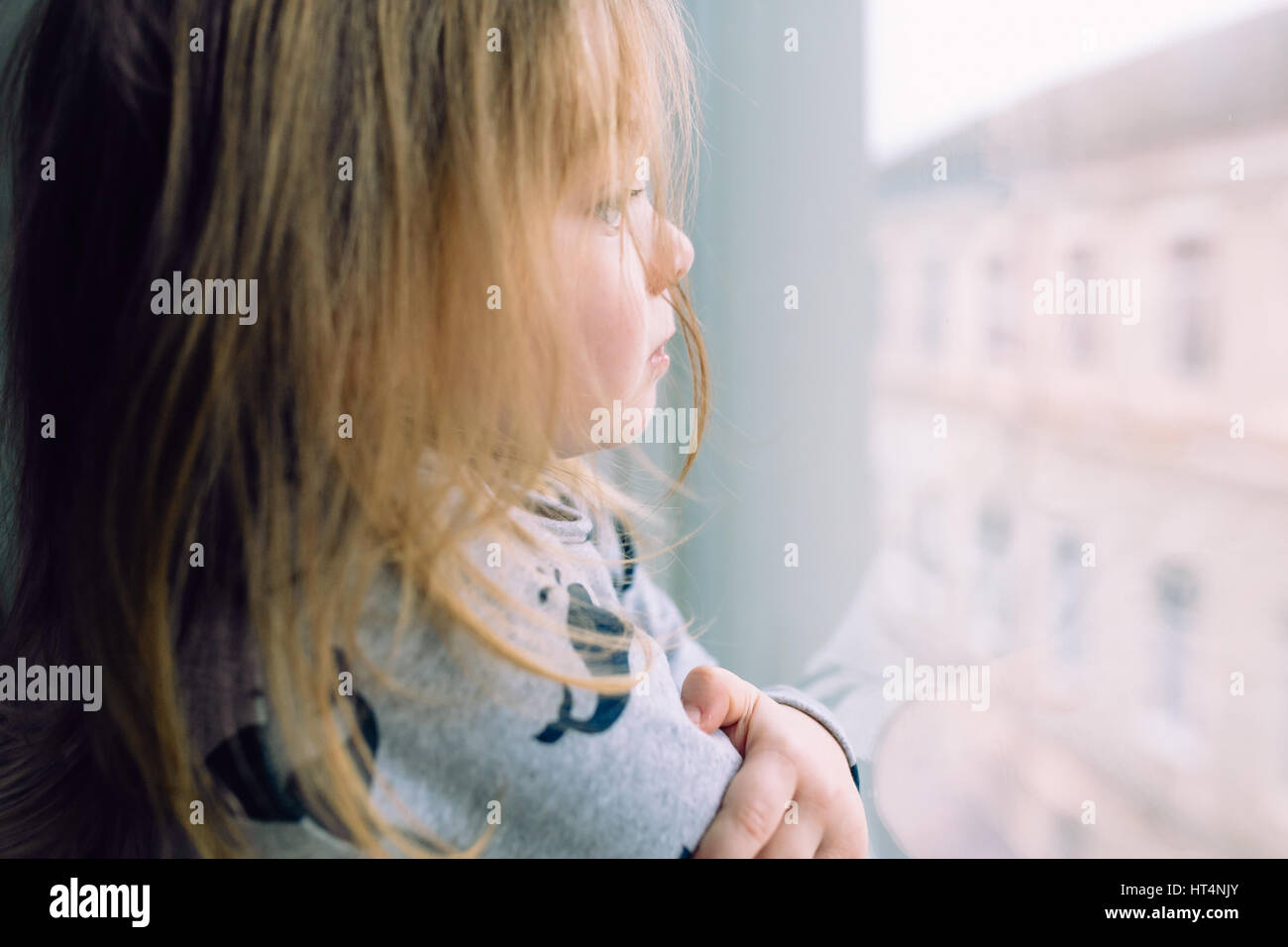 Hopeless life. Close up of depressed poor little girl standing near window and looking - Stock Image