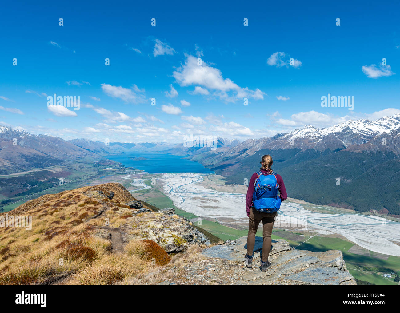 Hiker overlooking Lake Wakatipu from Mount Alfred, Glenorchy at Queenstown, Southern Alps, Otago, Southland, New - Stock Image