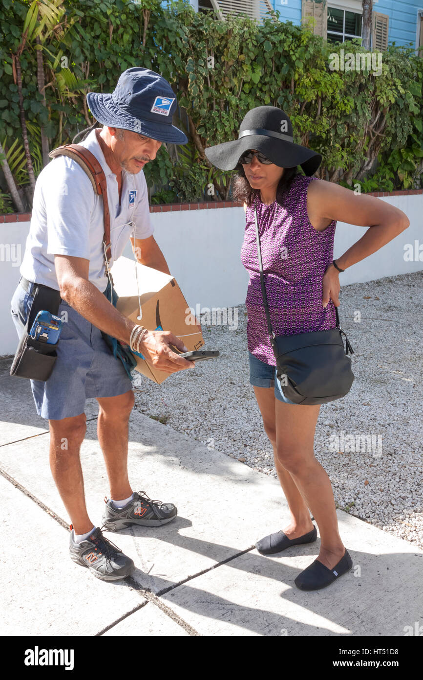 U.S. Postal Worker delivering package to woman. - Stock Image