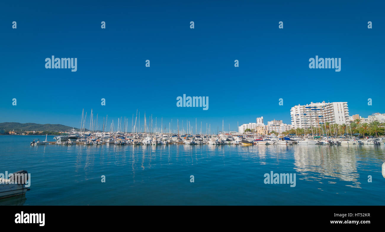 Boats, small yachts and water craft of all size in Ibiza marina harbour.  Bright white City of  St Antoni de Portmany. - Stock Image