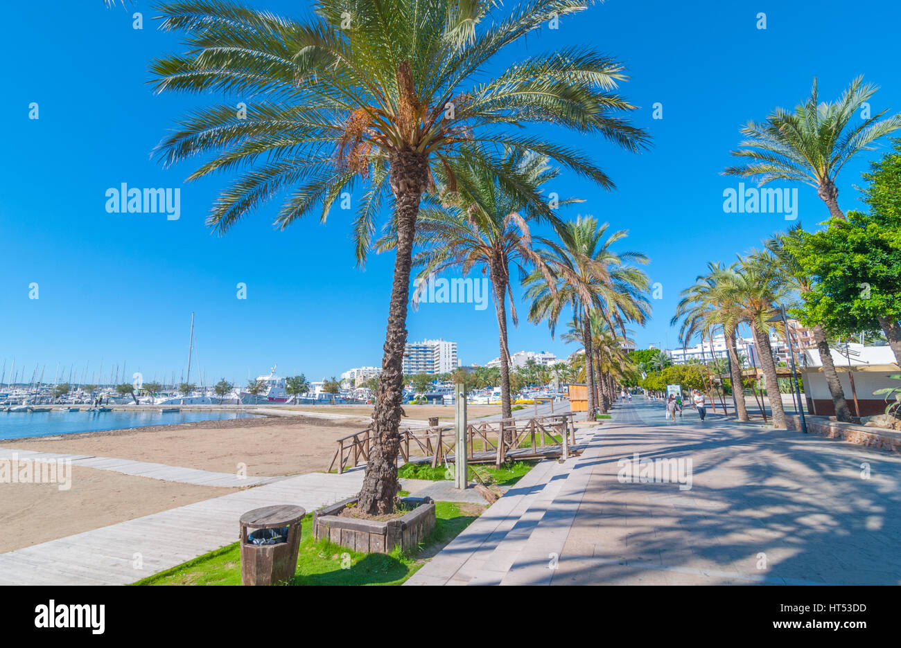 Sant Antoni de Portmany, Ibiza, Nov 6th, 2013.   Touring Ibiza in sunshine.   People walk along main boardwalk, - Stock Image