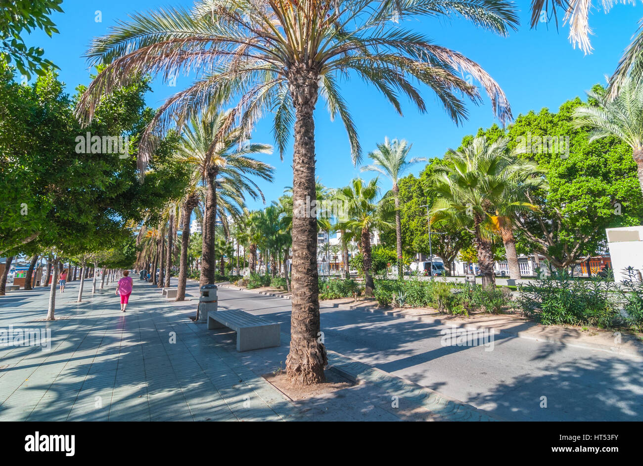 Two women walk along main boardwalk, now a stone concourse, beside the beach in street of Sant Antoni de Portmany, - Stock Image