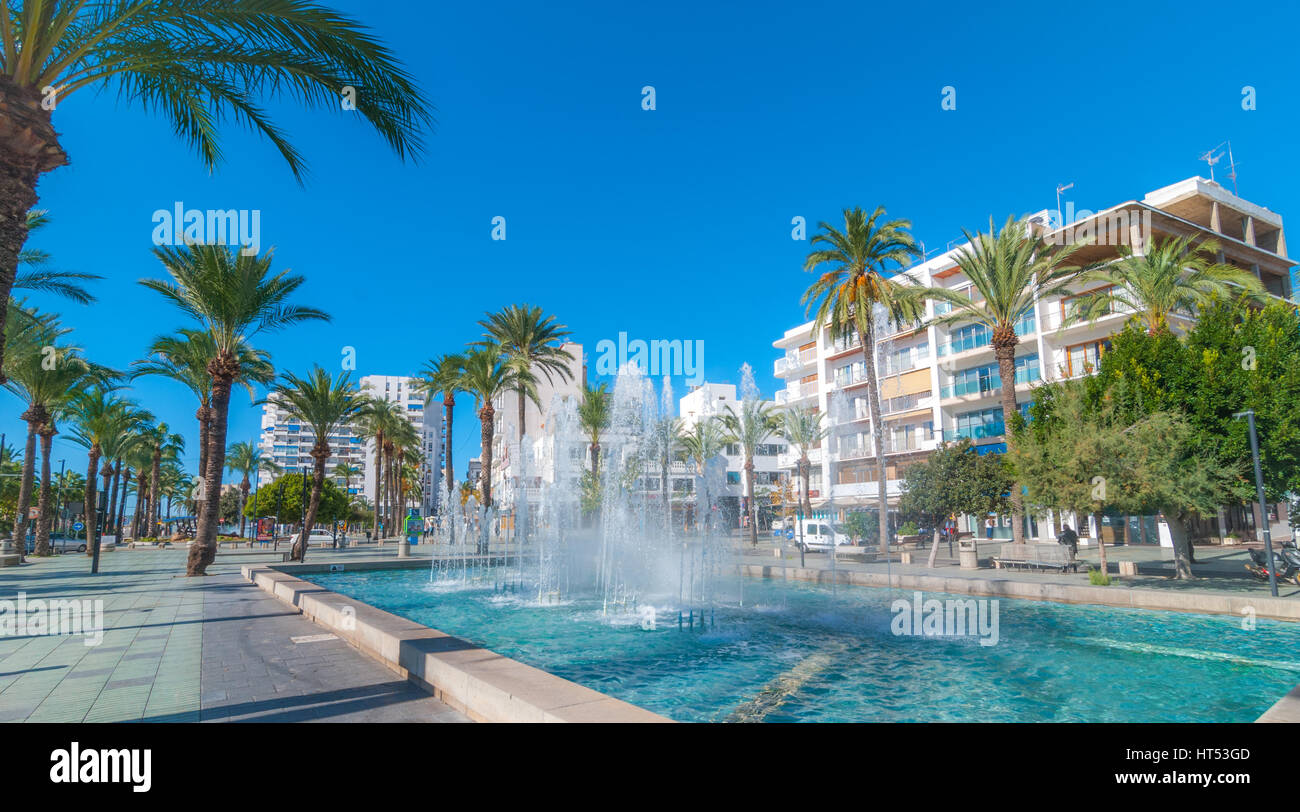 Bright morning sunshine on town square pedestrian park & fountain.  Hotels in background.  Lovely Fountain park - Stock Image