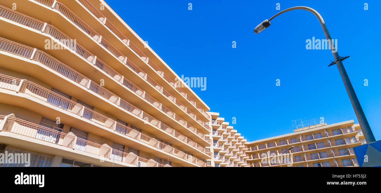 Abstract of sunlit building balcony line uniformity, street lamp in daytime.  Hotel exterior & facade with balconies. - Stock Image