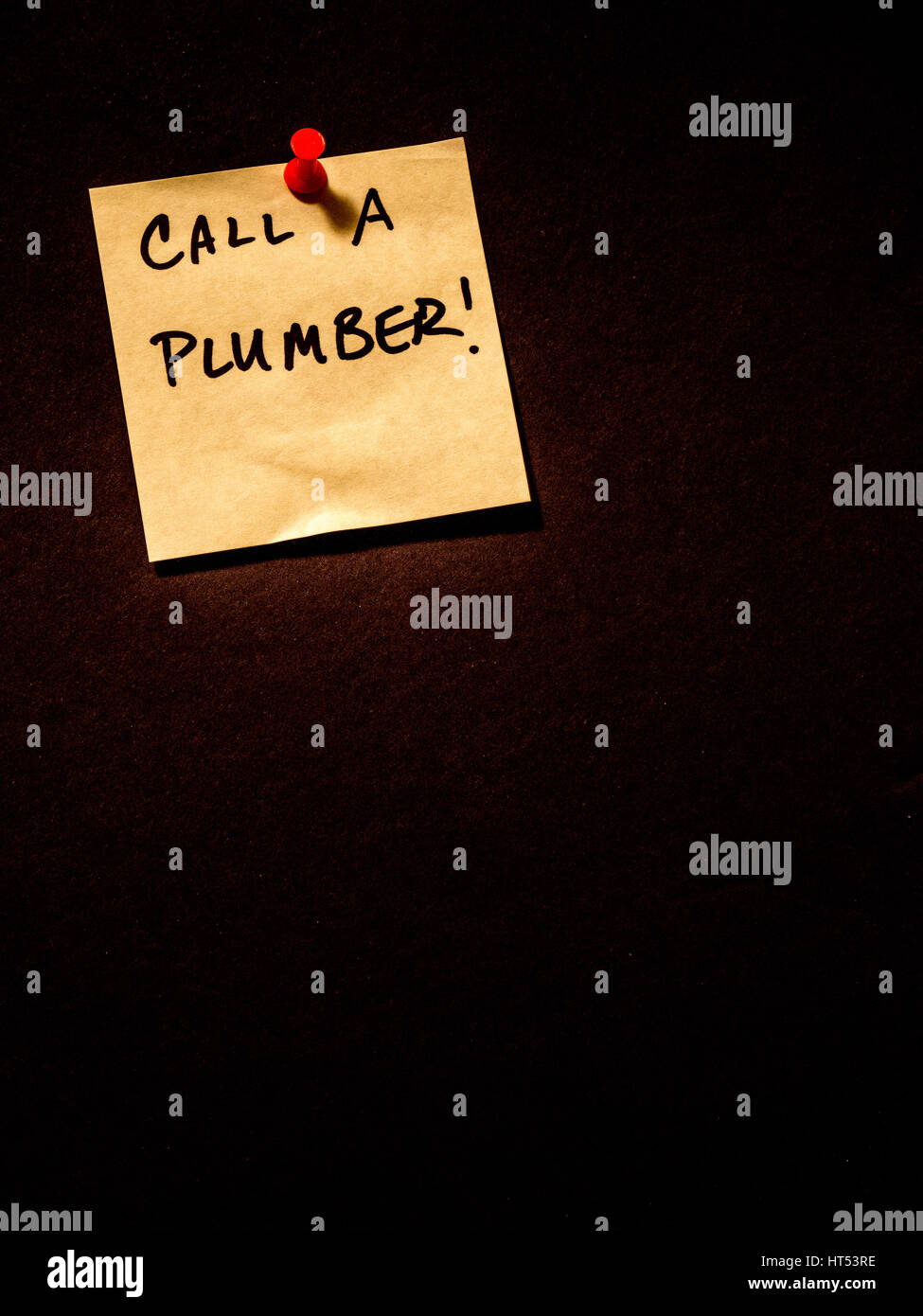 Call a plumber, post it note on black, portrait orientation - Stock Image