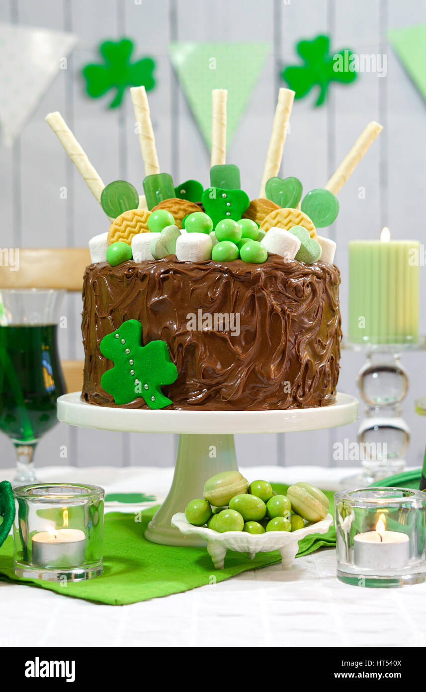 Happy St Patricks Day, March 17, green and white party table with showstopper chocolate cake decorated with candy, - Stock Image