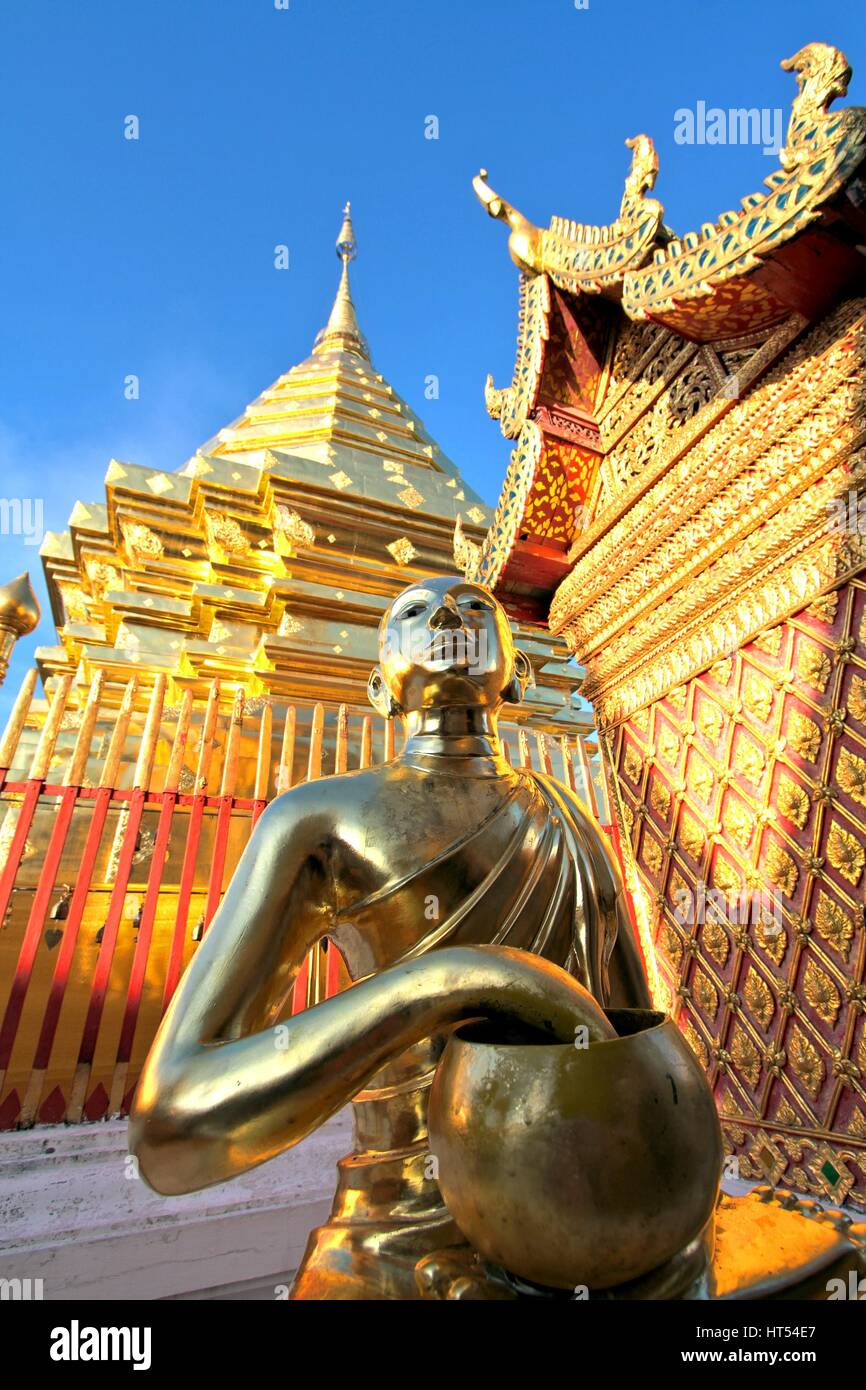 Golden buddha statue and pagoda against clear blue sky at Wat Phra That Doi Suthep, A famous Theravada buddhist - Stock Image
