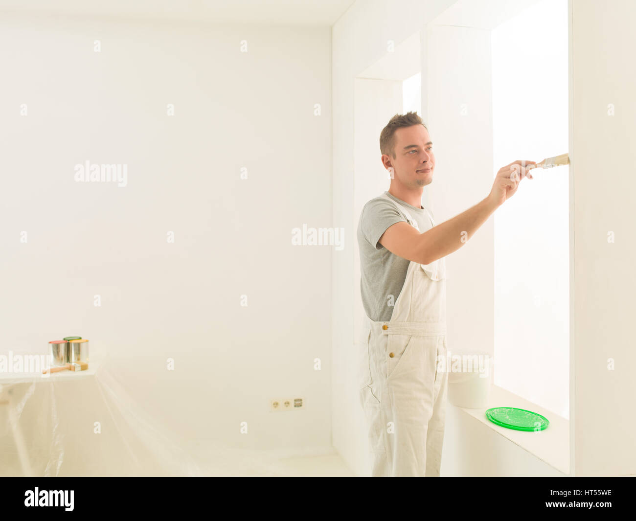 handsome men painting his luminous home-office - Stock Image