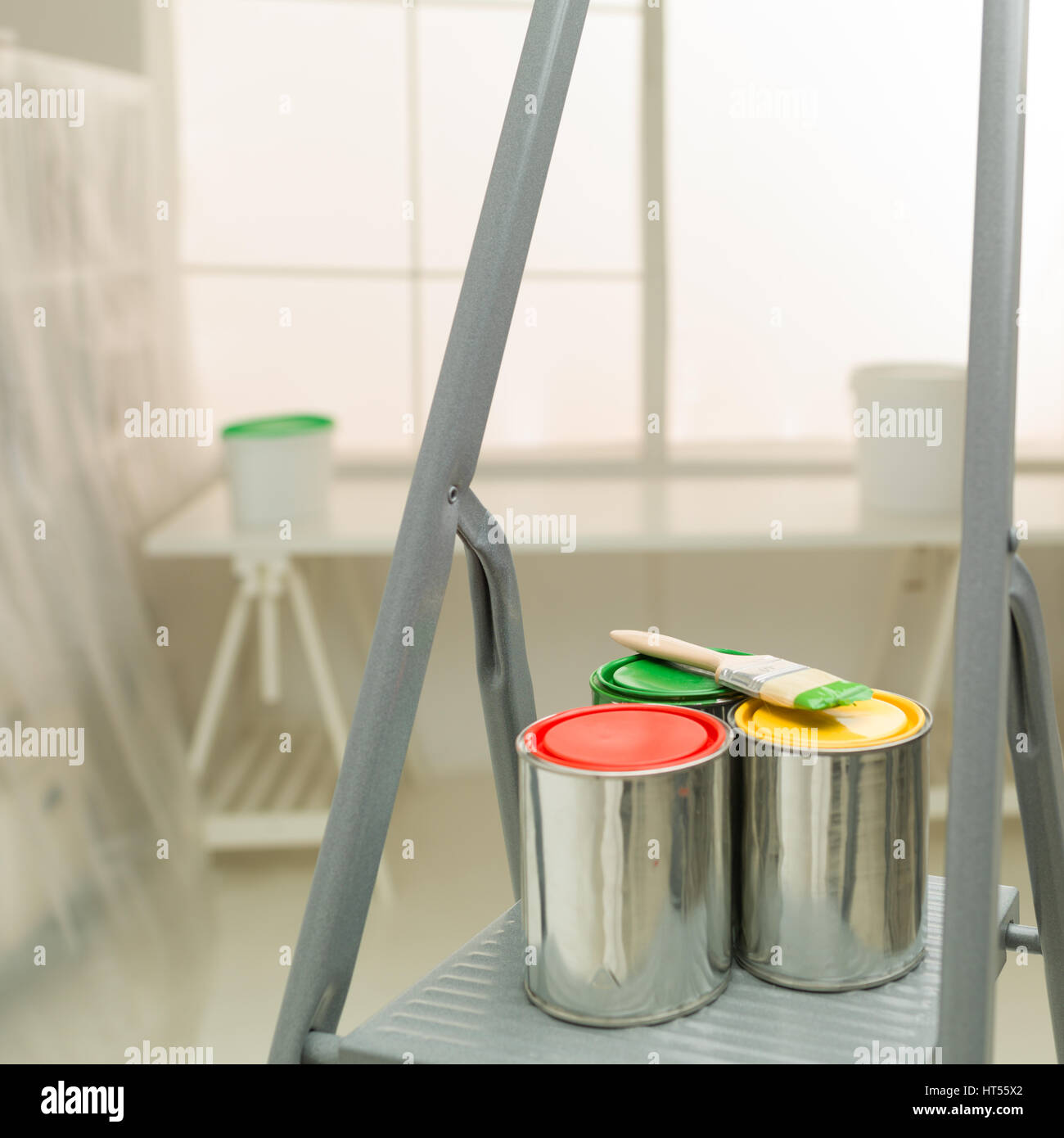 colourful cans of paint on a stepladder window in background ; home improvement concept - Stock Image