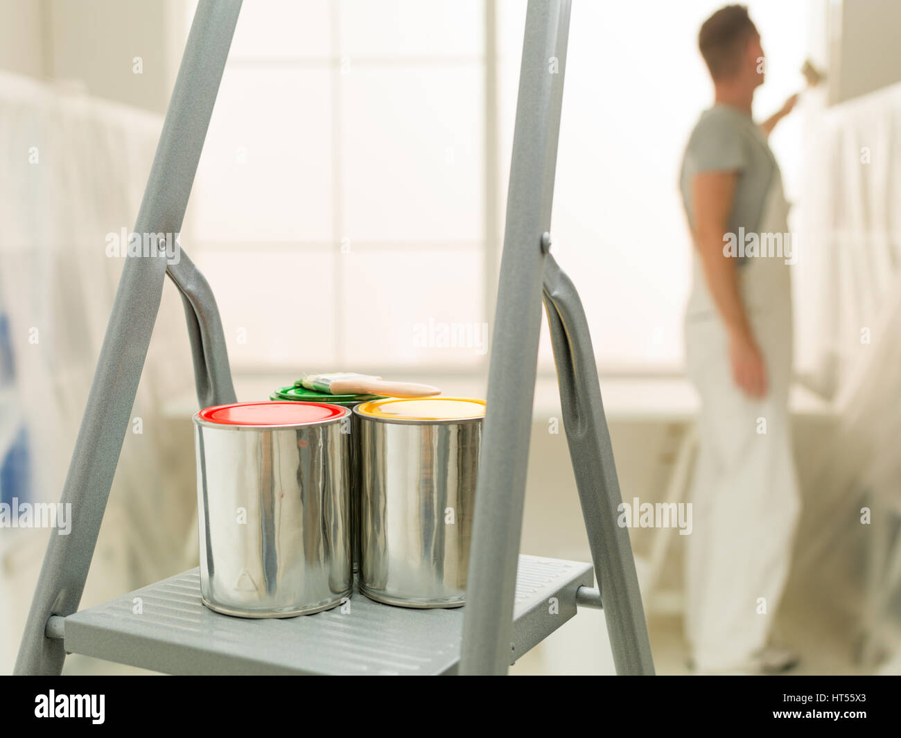 colourful cans of paint on a stepladder young decorator painting in background blurred; home improvement - Stock Image