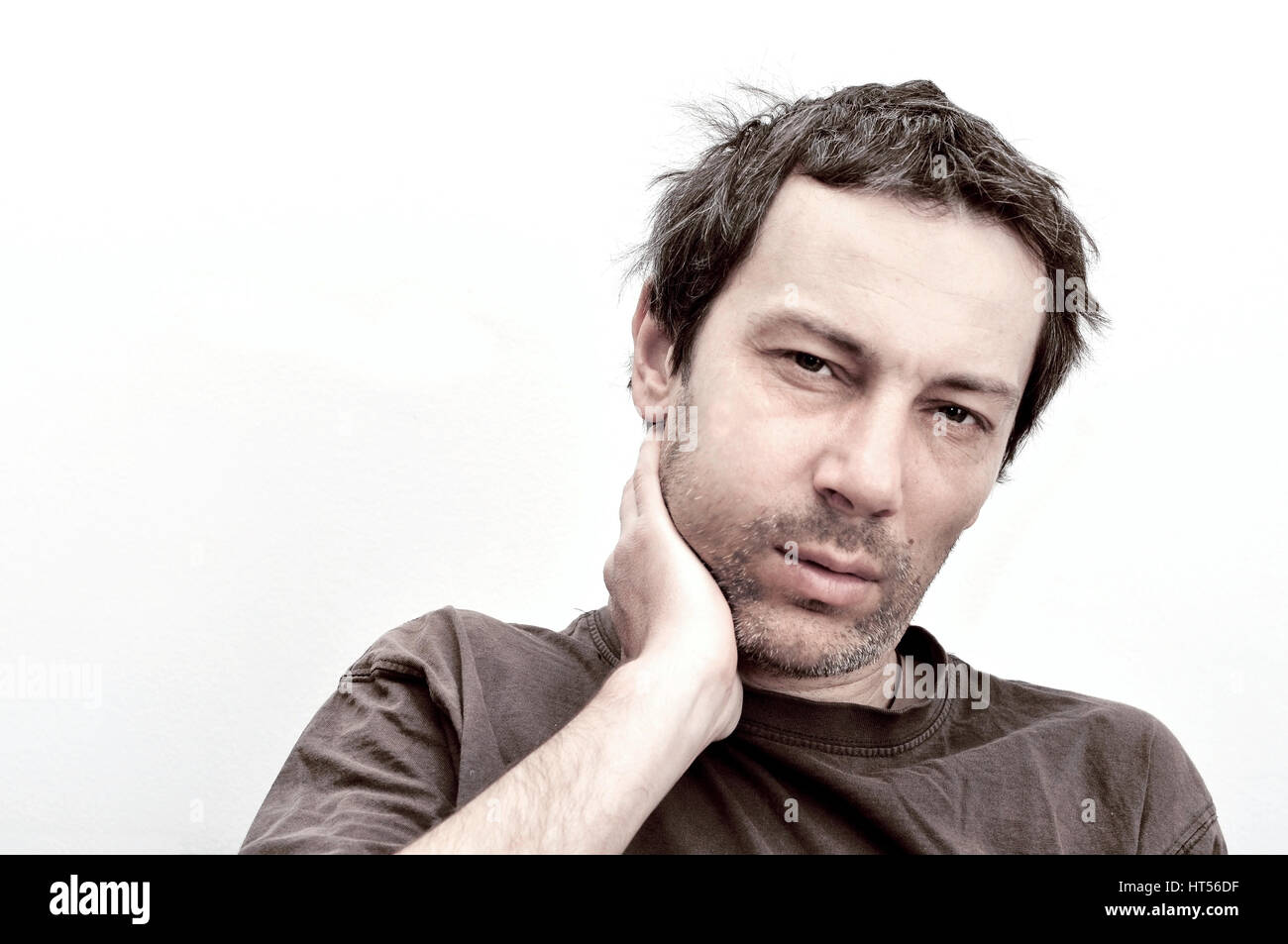 Young man suffering from toothache, teeth pain, swelling face - Stock Image