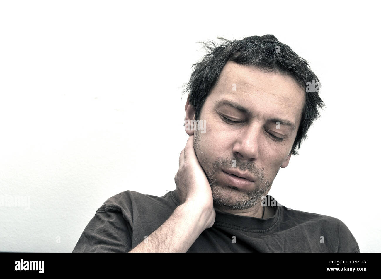 Young man suffering from toothache, teeth pain, swollen face - Stock Image