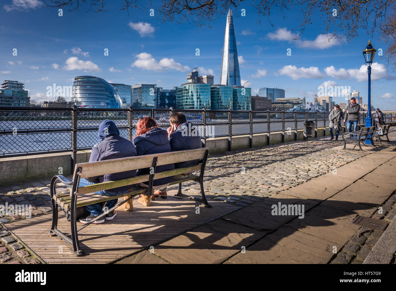 People enjoy the sunshine on the pathway outside the Tower of London on a cold but bright day in the capital city Stock Photo
