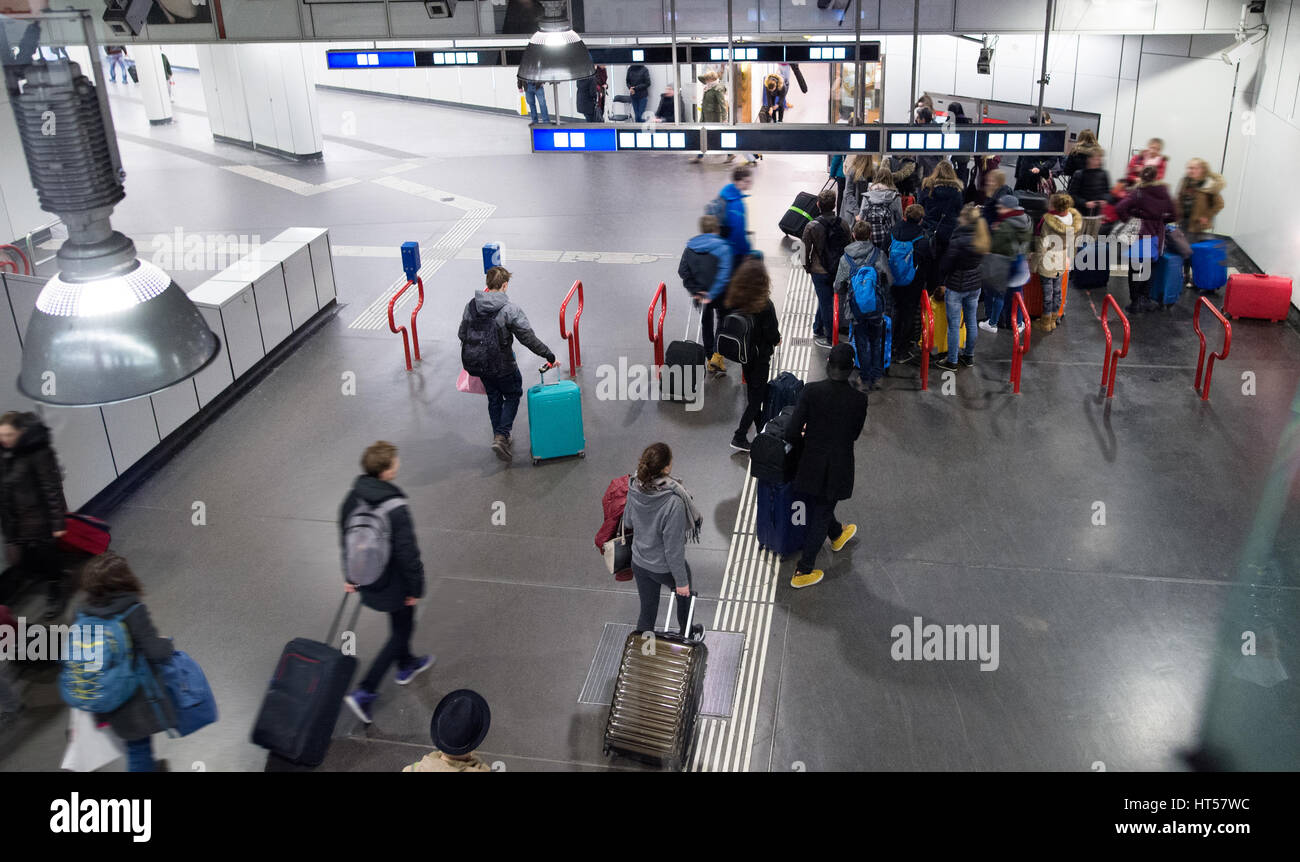 Travellers walk through train station carrying suitcases, Vienna, Austria. Stock Photo