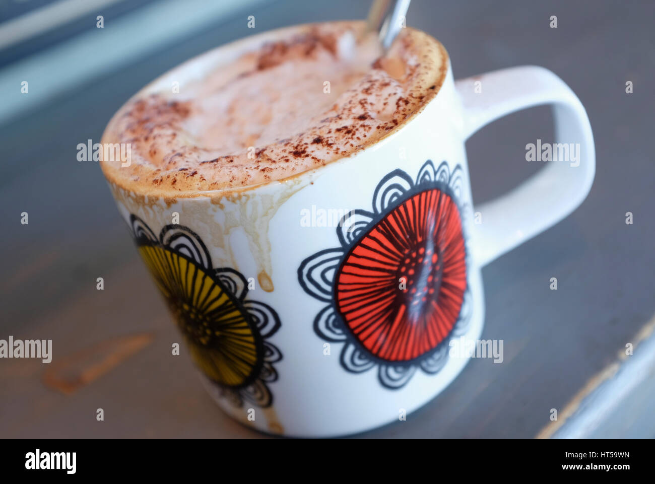 homemade cappuccino coffee in floral design mug - Stock Image