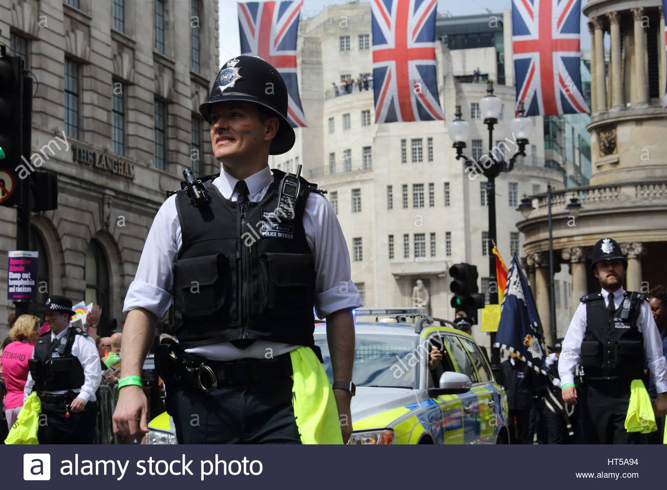 A British police officer smiles as he participates in the 2016 London Pride festival Credit: reallifephotos / Alamy - Stock Image