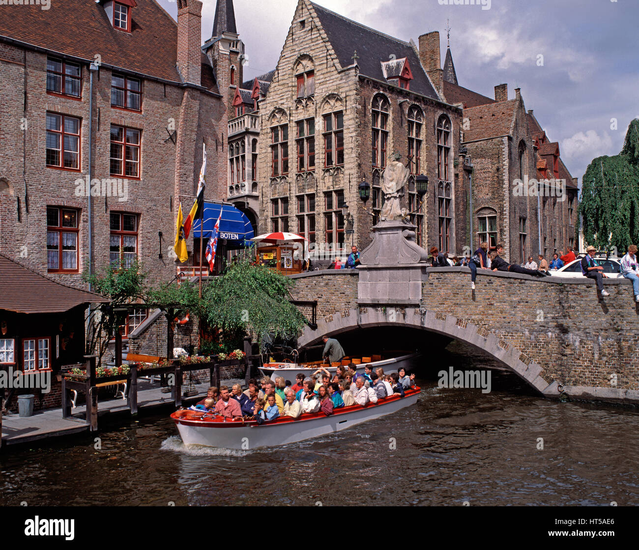 Tourist boat passing under a bridge over the Dijver Canal, Bruges, Belgium. - Stock Image