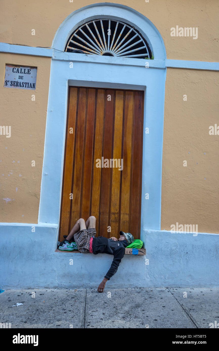 MAN LYING IN WINDOW COLORFUL PAINTED BUILDING CALLE SAN SEBASTIAN OLD SAN JUAN PUERTO RICO - Stock Image