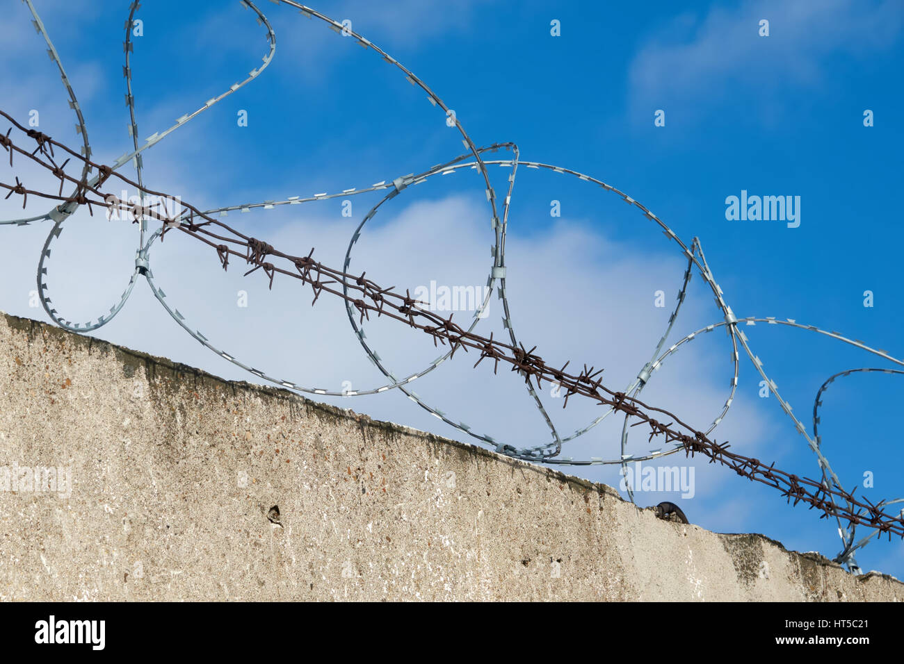 Fence with barbed wire. Blue sky. Clouds - Stock Image