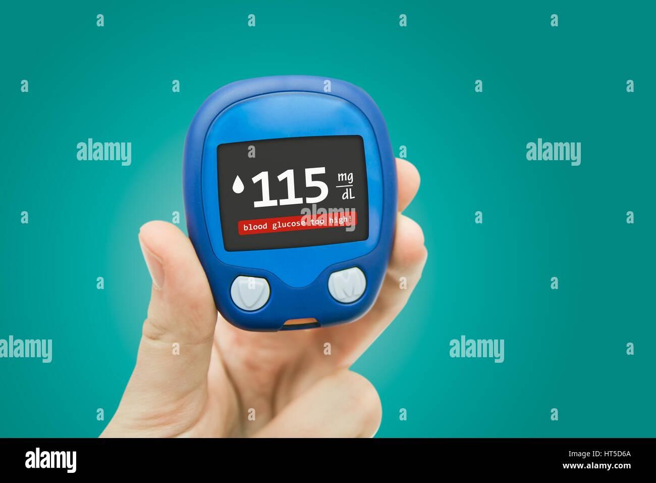 Hand holding meter. Diabetes doing glucose level test. Medical background concept - Stock Image