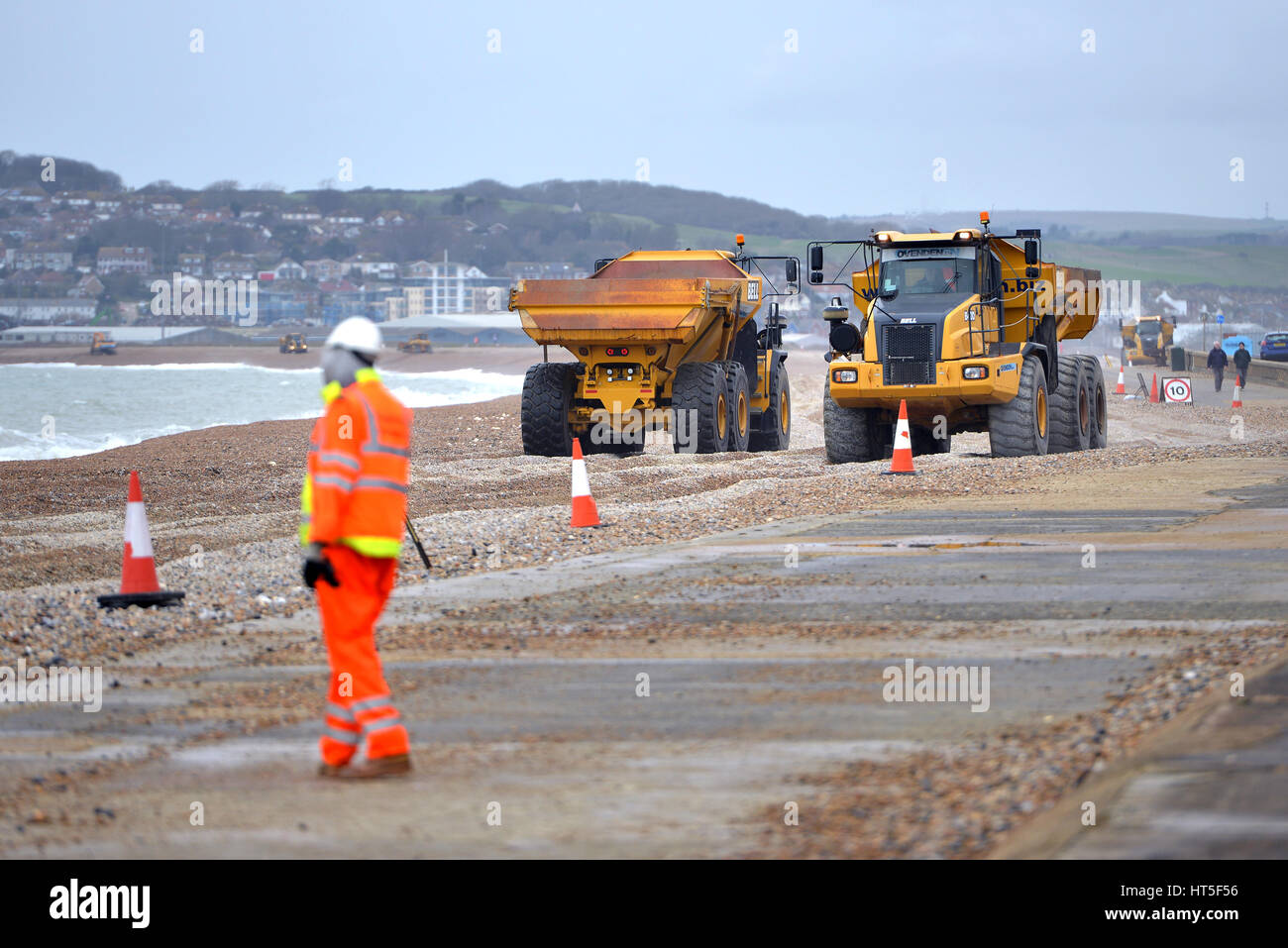 Beach repairs - Moving shingle along Seaford beach after winter storms washed away the pebbles. - Stock Image
