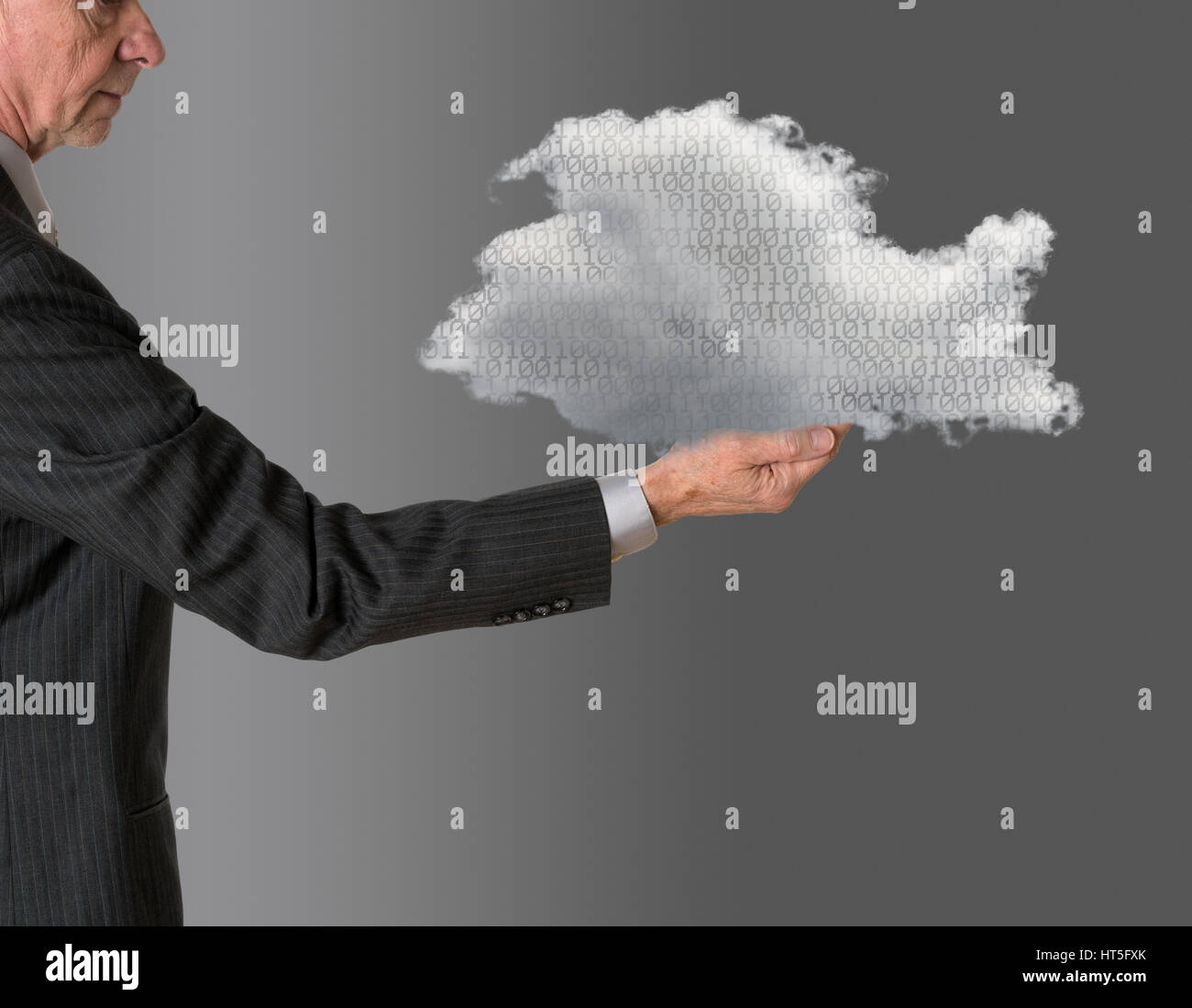 Senior male caucasian executive holding cloud computing shape. Connection to electronic records via WiFi to web - Stock Image
