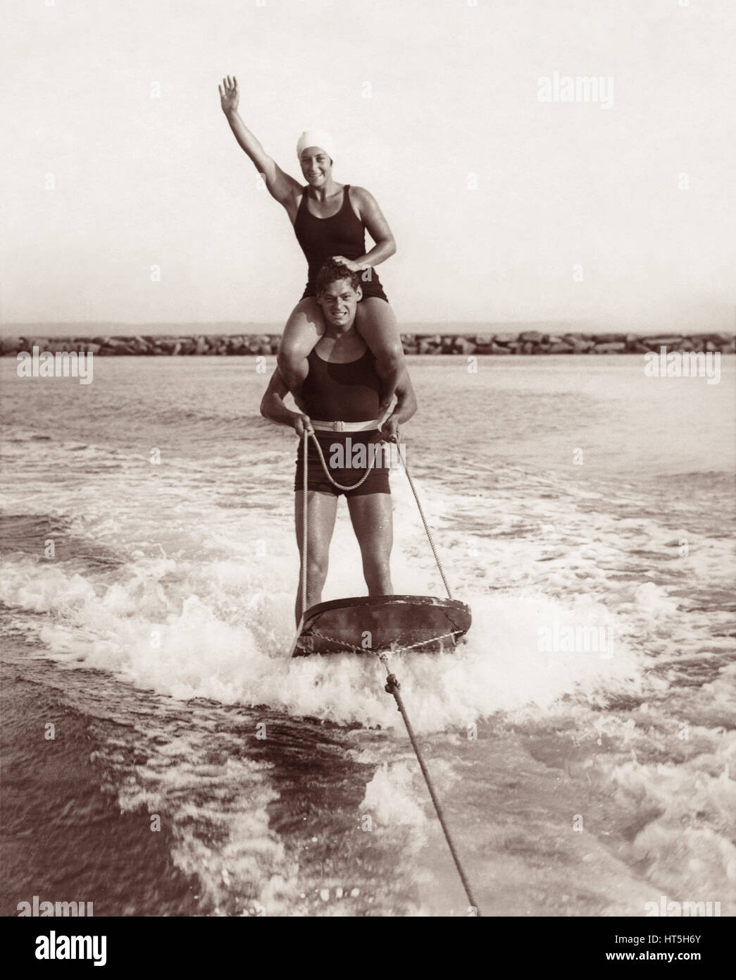 Olympic champions Johnny Weissmuller (Tarzan) and Helen Meany aquaplaning behind a motorboat in Long Island Sound - Stock Image
