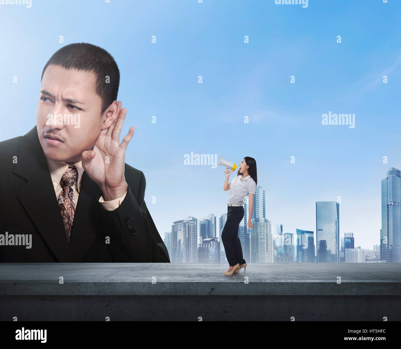 Business woman using megaphone say something to boss with cityscape background - Stock Image