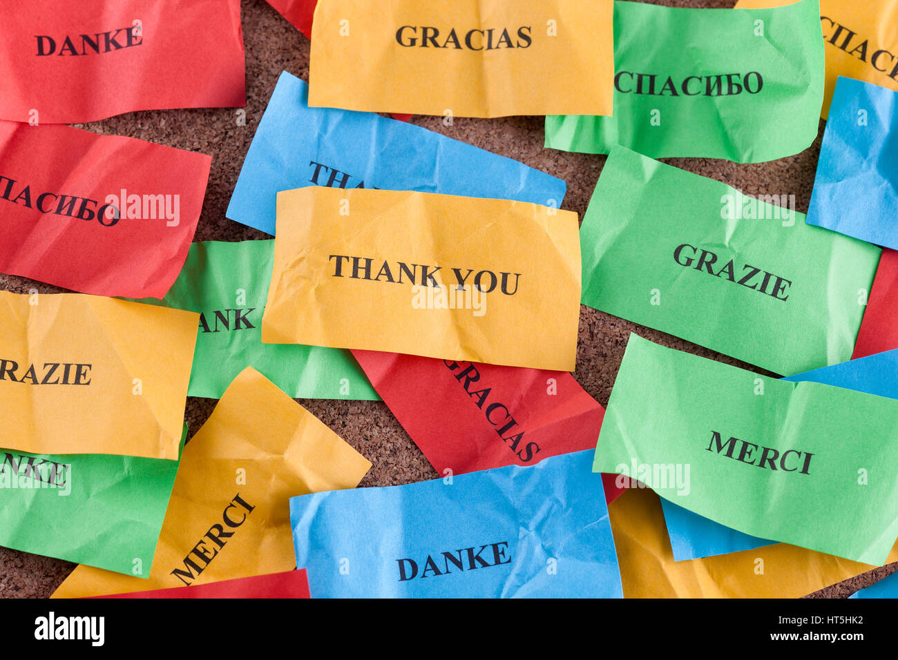 Thank you in many languages on colorful pieces of paper. - Stock Image