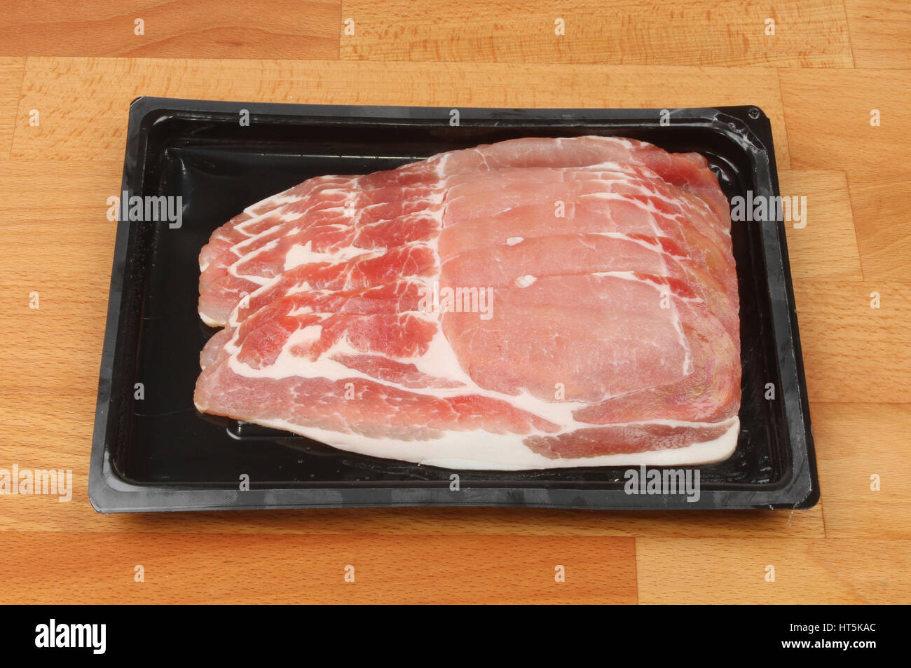 Bacon rashers in a plastic carton on a wooden kitchen worktop - Stock Image